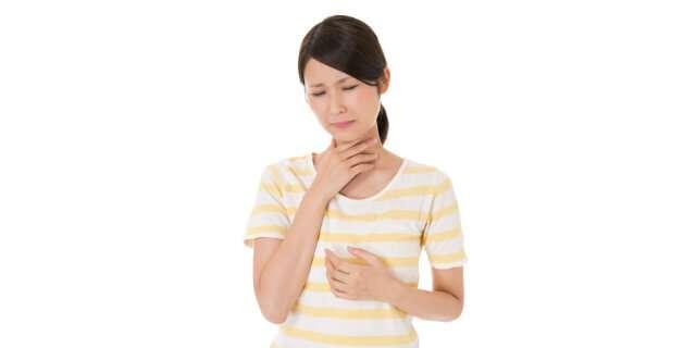 喉を痛そうにする女性