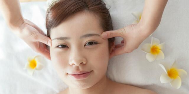 耳のつぼを押される女性