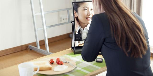 朝食と鏡を見る女性