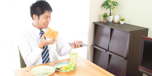 テレビを見ながら食べる男性
