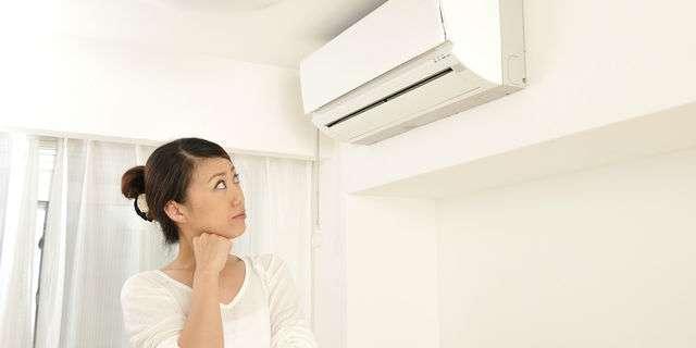 エアコンを見る主婦