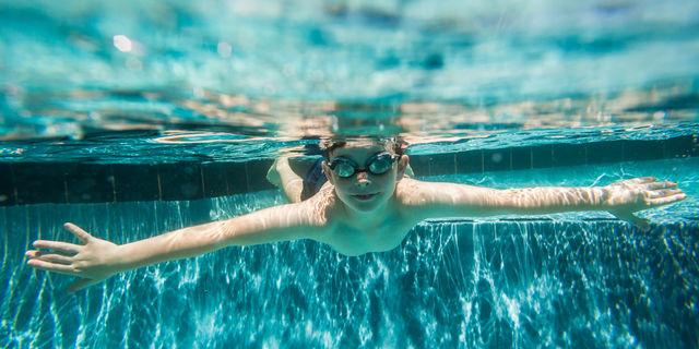 プールの中に潜る海外の少年